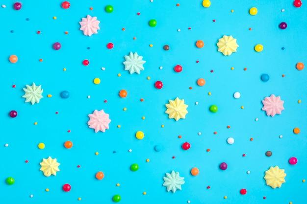 Patrón sin fisuras de mezclar dulces coloridos - piruleta, merengue, chocolate, dulce espolvorear sobre fondo azul.