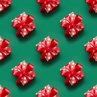 Patrón sin fisuras de regalos en envases rojos y blancos con lunares y lazo rojo en el espacio verde