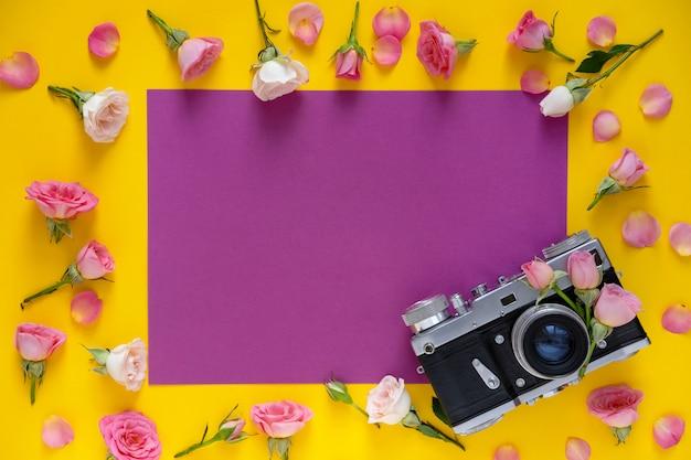 Patrón floral de marco redondo hecho de rosas rosadas y beige, hojas verdes y cámara de película sobre fondo amarillo. fondo del día de san valentín. vista plana, vista superior.