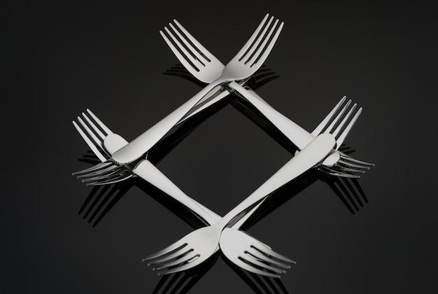 Patrón en forma de un diamante con muchos tenedores de plata sobre un fondo de espejo negro. concepto, textura.