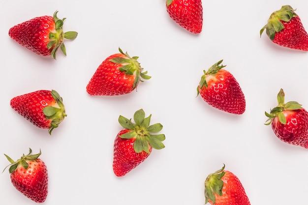 Patrón con fresas maduras sobre fondo blanco