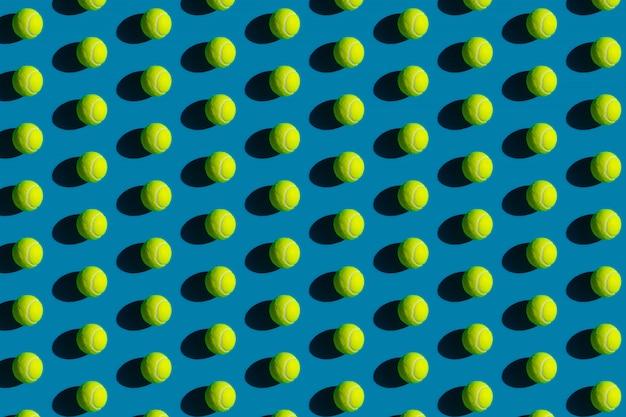 Patrón geométrico de pelotas de tenis con sombras fuertes sobre un fondo azul.