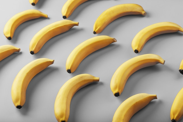 Patrón geométrico de plátanos amarillos sobre un fondo gris en los colores de moda