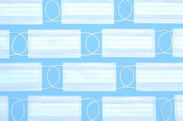 Patrón de máscaras médicas desechables azules sobre un fondo azul. protección contra el coronavirus covid-19.