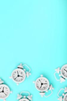 Un patrón de muchos despertadores clásicos blancos en forma de un patrón sobre un fondo azul. vista superior con una copia del espacio, plano.
