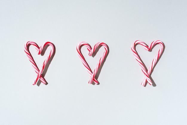 Patrón de navidad de bastón de caramelo con forma de corazón sobre fondo blanco.