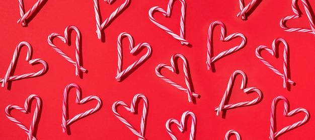 Patrón de navidad de bastón de caramelo con forma de corazón sobre fondo rojo.