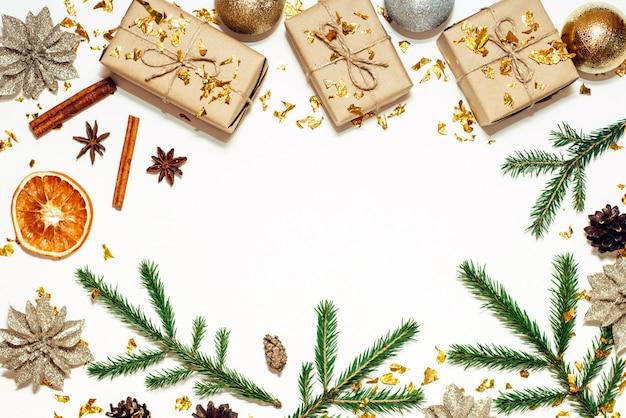 Patrón navideño con marco de piñas, ramas de abeto, bolas brillantes, cajas de regalo, anís estrellado, naranja seca y confeti