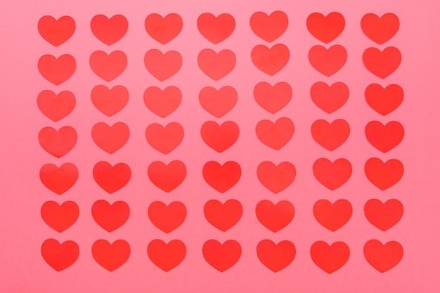 Patrón de pequeños corazones rojos sobre un fondo rosa