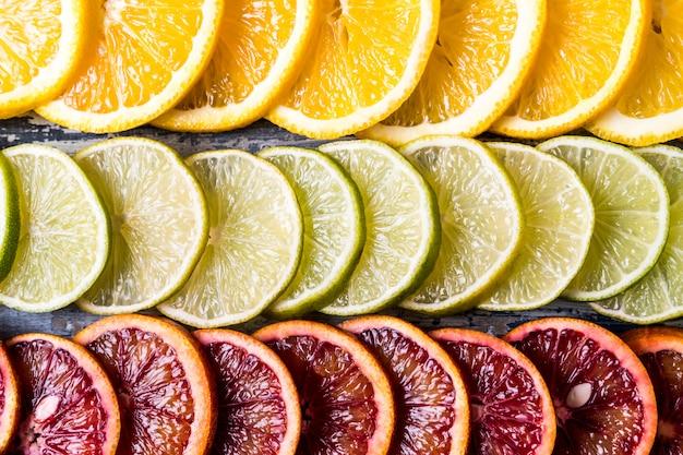 Patrón con rebanadas frescas de diferentes frutas cítricas - frutas naranjas rojas y amarillas, lima, pomelo. lay flat.