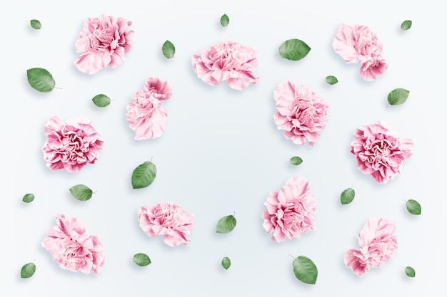 Patrón de rosas rosadas y beige y hojas verdes sobre un fondo blanco.