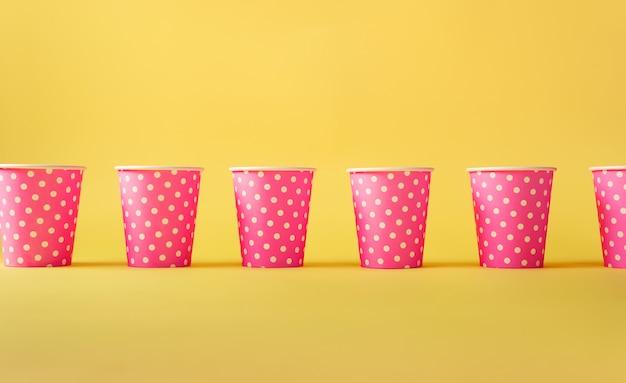 Patrón de tazas de papel de lunares rosa sobre fondo amarillo.