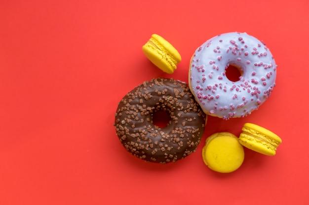 Patrón transparente hecho de macarrón y donut en el fondo rojo
