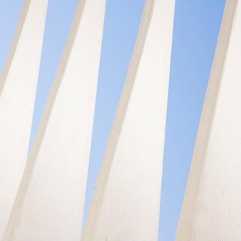 Patrón triangular de pared blanca contra el cielo azul.