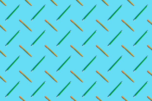 Un patrón vibrante de bolígrafos naranjas y lápices verdes. el concepto de oficina, negocios, creatividad, formación. fondo azul, vista superior, endecha plana.