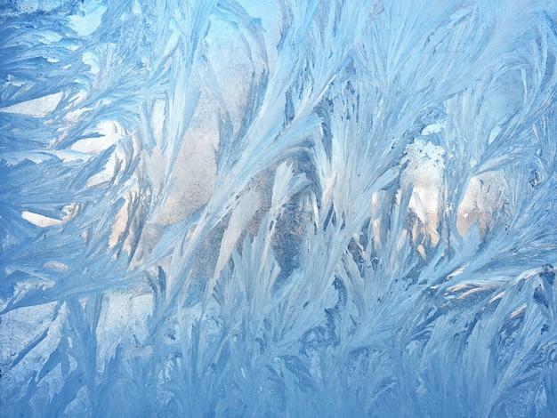 Patrones helados en el primer plano de cristal de la ventana. texturas y fondos naturales. patrones de hielo en congelado