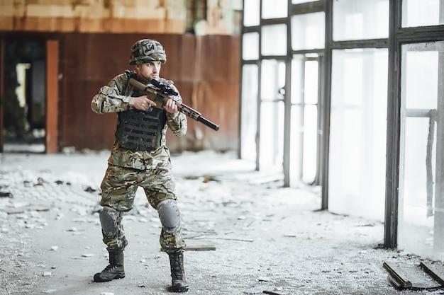 Patrulla el territorio. el joven soldado en el ejército se para en la ventana del edificio derrumbado. en la cabeza hay un casco protector. ¡hay una gran pistola en sus manos!