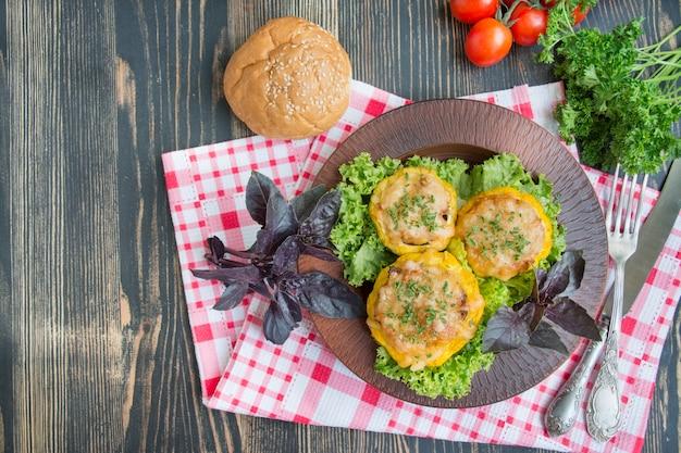 Patty pan squash al horno relleno de carne y queso, decorado con hierbas. calabacín al horno. fondo de madera menú de verano copia espacio cocinar. menú de fondo de la tabla.