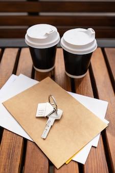 Pausa para el café: dos tazas en un vaso de plástico. inmuebles, llaves del inquilino de un apartamento o casa, compra y venta de inmuebles. hipoteca para la compra de un piso.
