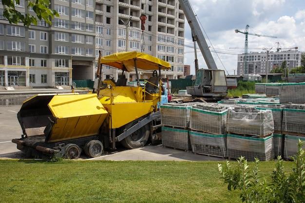 Una pavimentadora de asfalto está estacionada en un sitio de construcción. la maquinaria de construcción de carreteras se encuentra junto a la carretera en un almacén. construcción de carreteras pesadas y reparación de calles de la ciudad.