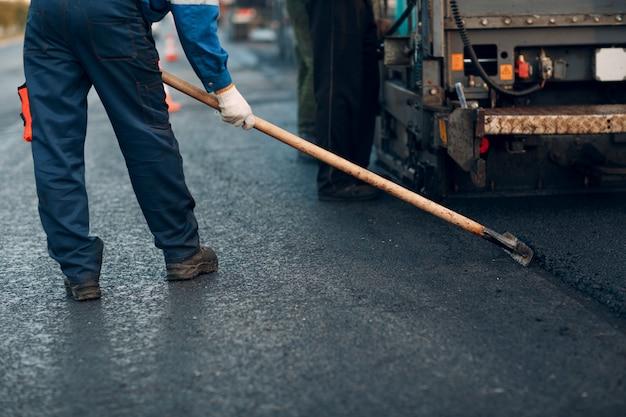 Pavimento de asfalto. máquina pavimentadora y apisonadora. nueva construcción de carreteras.