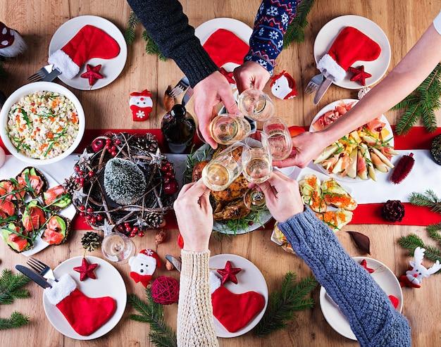 Pavo al horno. cena de navidad. la mesa navideña se sirve con un pavo, decorado con oropeles brillantes y velas. pollo frito, mesa. cena familiar. vista superior, manos en el marco