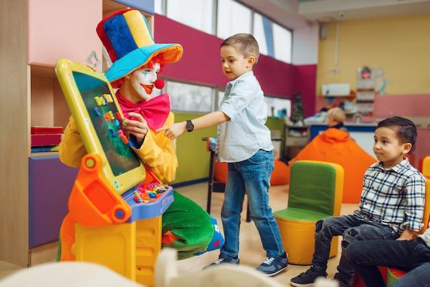 Payaso divertido con niños alegres jugar en el alfabeto a bordo.