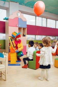 Payaso divertido con niños juegan en el alfabeto.