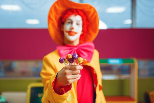 Payaso divertido con piruletas en la mano posa en el área infantil.