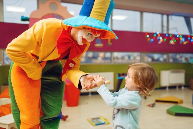 Payaso divertido reparte piruletas a la niña feliz, amistad para siempre. fiesta de cumpleaños celebrando en la sala de juegos, vacaciones para bebés en el patio de recreo.
