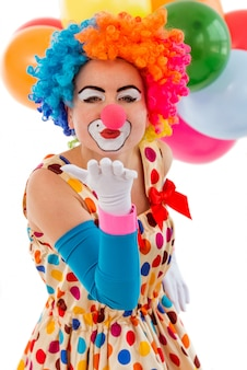 Payaso femenino juguetón divertido en peluca colorida besos al aire.