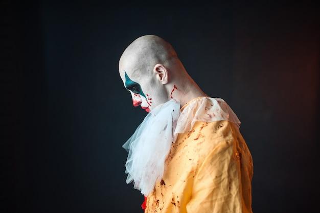 Payaso sangriento triste con maquillaje en traje de carnaval, vista lateral