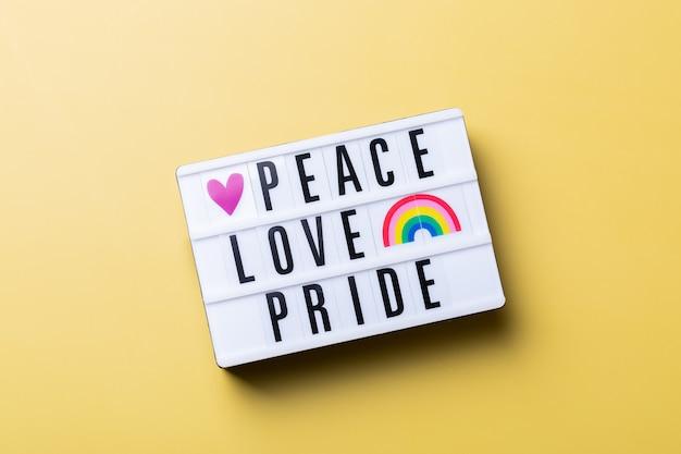 Paz, amor, orgullo, texto, arco iris, lgbtq, bandera, contra, fondo amarillo