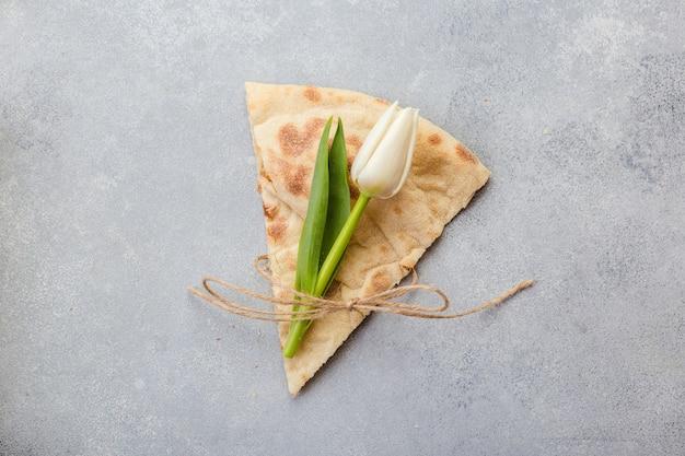 Paz creativa de pizza con flores tulipanes en gris