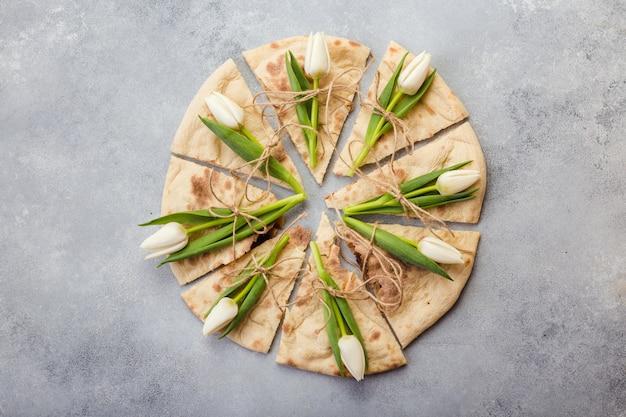 Paz creativa de pizza con flores tulipanes en placa