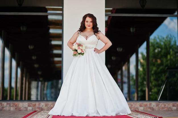 Pechos grandes morena novia con ramo de novia posó en el salón de bodas en la alfombra roja