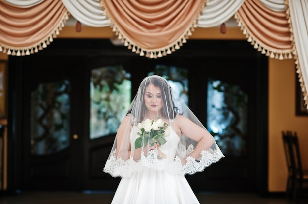 Pechos grandes morena novia con ramo de novia posó bajo velo en el salón de bodas