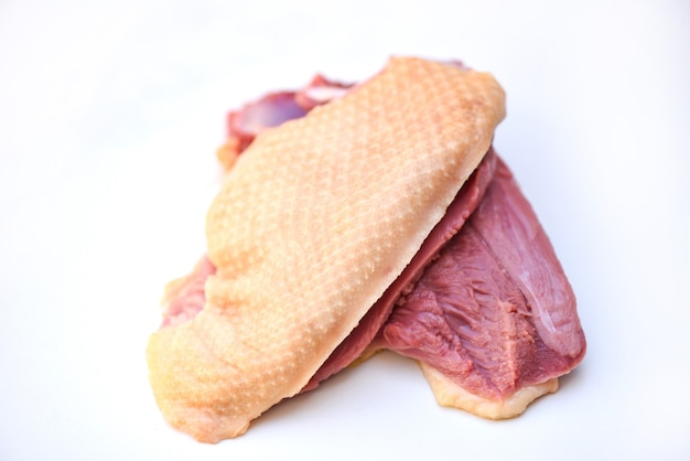 Pechuga de pato cruda sobre fondo gris blanco, carne de pato fresca para la alimentación