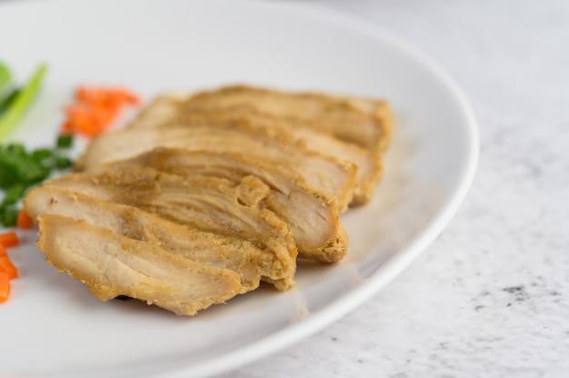 Pechuga de pollo al vapor en un plato blanco con cebolletas y zanahorias picadas