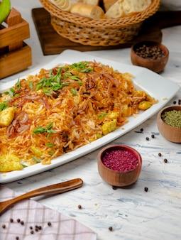 Pechuga de pollo, arroz con salsa de tomate, risotto, plov con hierbas, yogur y sumakh en un plato blanco