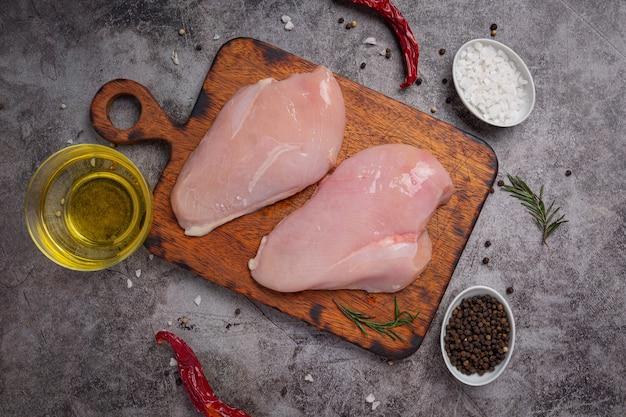 Pechuga de pollo cruda sobre la superficie oscura.
