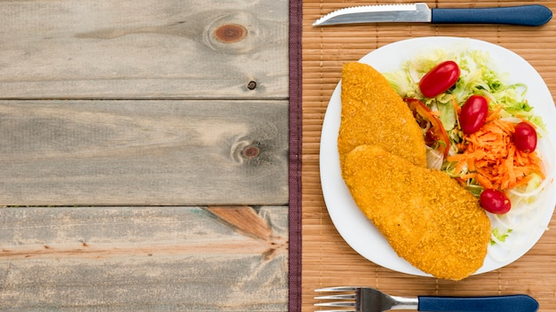 Pechuga de pollo frito y ensalada de col en un plato en la mesa de madera