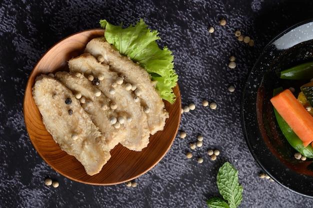 Pechuga de pollo a la parrilla, espolvoreada con pimienta, colocada en un plato de madera