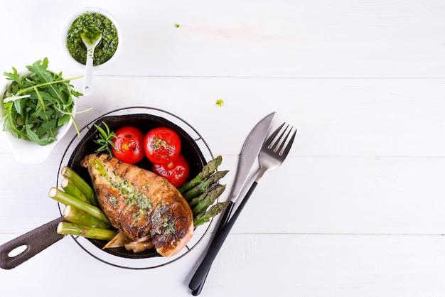 Pechuga de pollo a la parrilla en una sartén de hierro fundido con verduras a la parrilla y salsa verde sobre una endecha blanca y plana