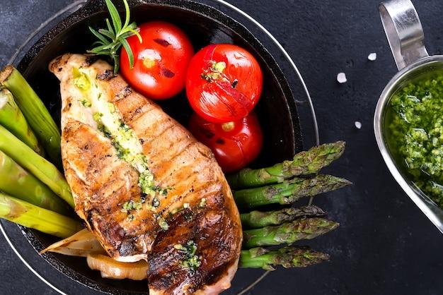 Pechuga de pollo a la parrilla en una sartén de hierro fundido con verduras a la parrilla y salsa verde sobre una piedra, aplanada