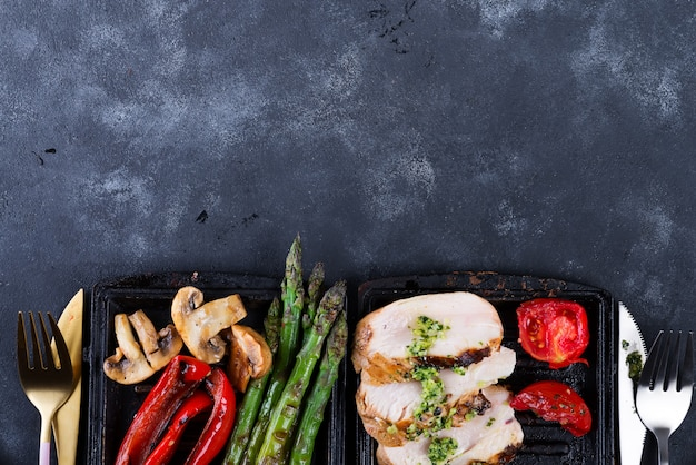 Pechuga de pollo a la parrilla en una sartén de hierro fundido con verduras a la parrilla sobre una piedra, aplanada