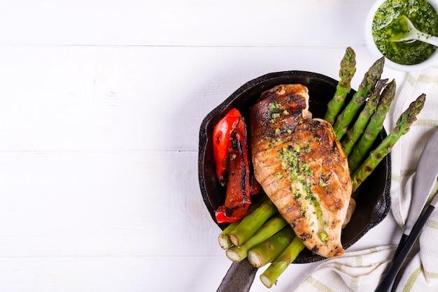 Pechuga de pollo a la parrilla con verduras a la barbacoa y salsa pesto en una sartén de hierro fundido en blanco
