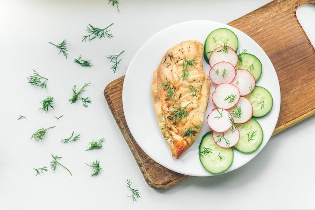 Pechuga de pollo y pepino en plato blanco sobre fondo de madera.
