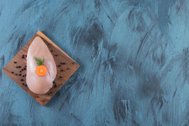 Pechuga de pollo sin piel sobre una tabla, sobre fondo azul.