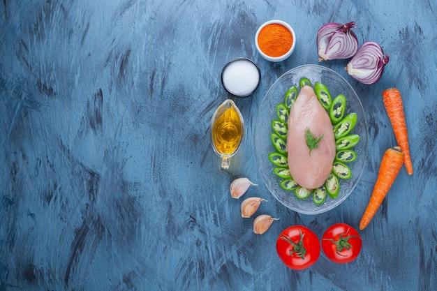 Pechuga de pollo y pimientos en rodajas en una placa de vidrio junto a especias, aceite y diversas verduras, en el azul.